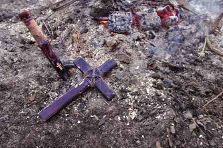 Wooden cross on the ash by fire...