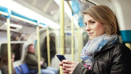 woman in subway train smiles towards something
