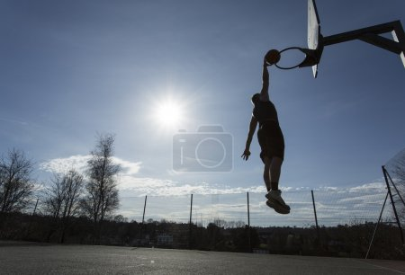 Silhouette Basketball player in mid air slam dunking on an outdoor basketball hoop