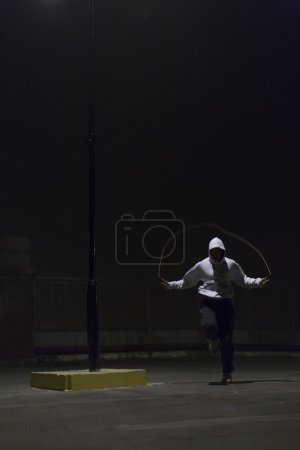 Athlete skipping at night with a jump rope