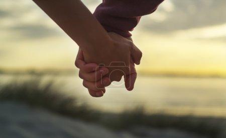 Tenue de couple mains sur une plage au coucher du soleil