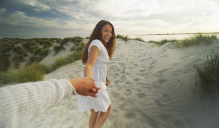 Young woman holds hands with the viewer on a sandy beach