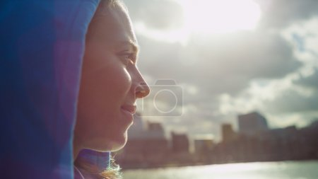 Portrait of attractive female runner in a hood looking across the city river on a sunny day with sun flare