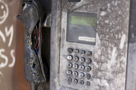 Vandalized pay phone, burnt and melted by arson