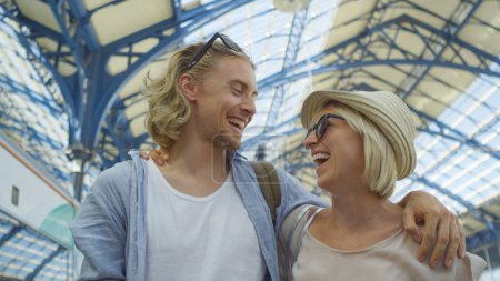 Attractive couple walk arm in arm in a train station whilst sharing a laugh together