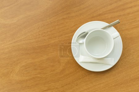 Empty white cup and saucer with a silver spoon and as ache of sugar on a wooden table