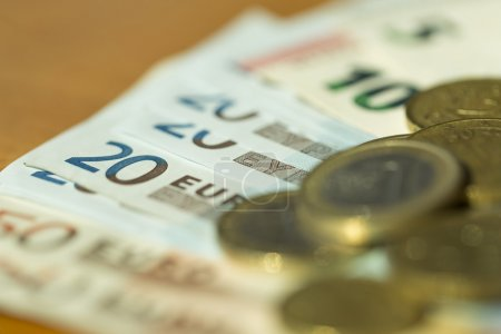 Euro notes and coins strewn across a table with very shallow focus