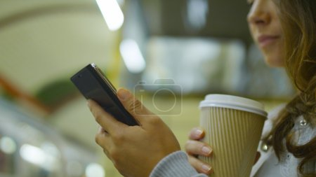 Female on her smart phone holding a cup of coffee at a train station