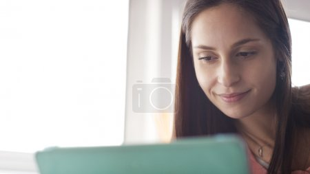 Attractive young woman smiling as she uses her digital tablet at home