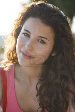 Portrait of a beautiful woman in a pink top smiling to camera
