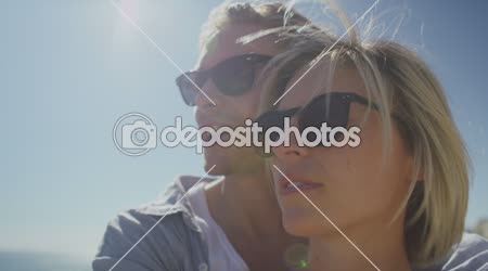 Couple in sunglasses enjoying the sea view and kissing