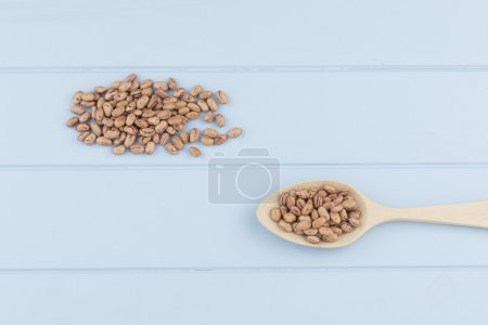 Some speckled beans and a spoon on a blue wooden table