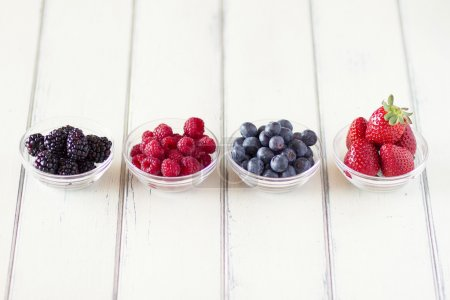 Bowl with blackberries, raspberries, blueberries and strawberries on white wooden