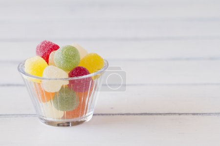 Colorful sweet jellies with sugar in a bowl on a white wooden table