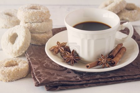 Pile of fresh donuts with cinnamon and star anise, a coffee cup and a brown napkin on a white wooden table