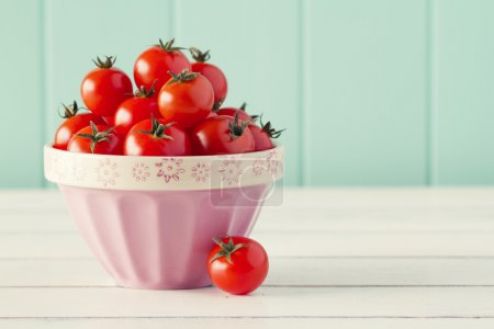 Several tomatoes in a pink bowl on a white wooden table with a robin egg blue background. Vintage look.