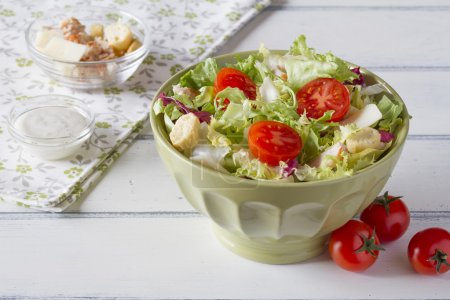 Cesar salad on a green bowl on a white wooden table with ingredients and a napkin