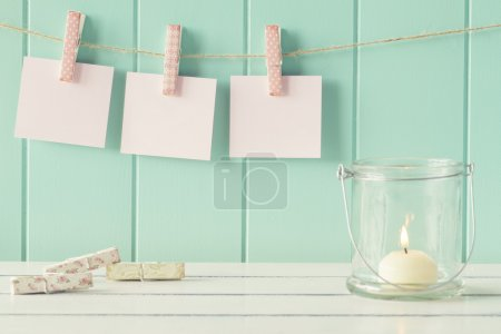 Three sheets of paper hanging on clothespins. Robin egg blue background. Vintage look.