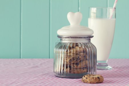 Glass jar with chocolate chip cookies and a glass of milk. Robin egg blue background. Vintage look.