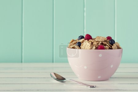 Pink bowl with cereals, raspberries and blueberries. Robin egg blue background. Vintage look.