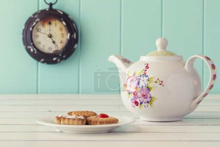 A teapot, a plate with some german cookies and a clock in the background. Five o'clock. Tea time. Robin egg blue background. Vintage look.