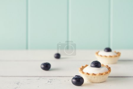 Closeup of tartlets with blueberries and greek yogurt on a white wooden table with a robin egg blue background. Vintage look.
