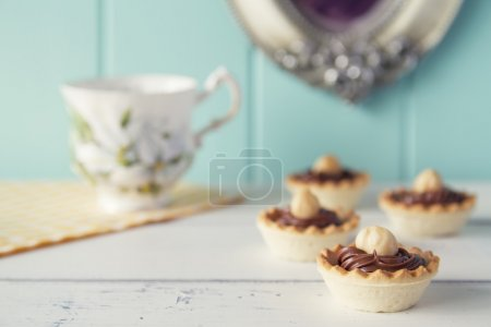 Closeup of tartlets with chocolate and hazelnut cream on a white wooden table with a robin egg blue background. Vintage look.