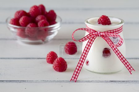 Delicious breakfast with yogurt and raspberries on a white wooden table