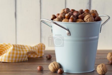 Walnuts and hazelnuts in shells on a turquoise bucket. A Yellow checkered napkin on a wooden table with a white wooden table background