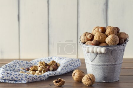 Walnuts and hazelnuts in shells on a metal bucket. A blue napkin on a wooden table with a white wooden table background