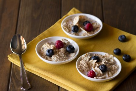 Three white bowls with cereals, raspberries and blueberries on a mustard yellow napkin over a wooden surface. Vintage look.
