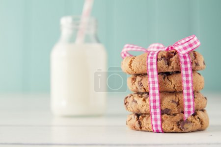 Chocolate chip cookies with a pink ribbon and a school milk bottle with a straw on a white wooden table with a robin egg blue background. Vintage look.
