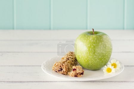 A apple on a plate with honey cereals bar on a white wooden table with a robin egg blue background. Vintage