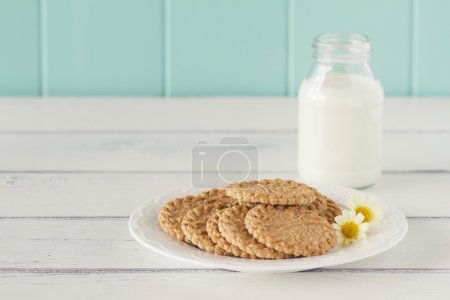 Some cereals cookies, a school milk bottle and a apple on a white wooden table with a robin egg blue background. Vintage