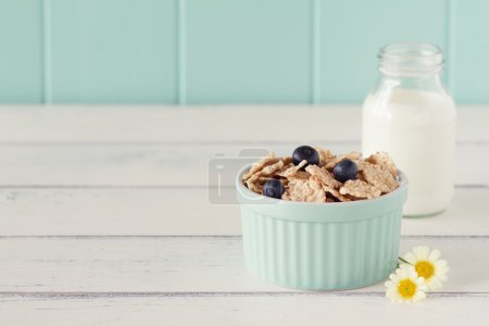 A turquoise classic whiteware baking bowl  with cereals and blueberries and a school milk bottle on a white wooden table with a robin egg blue background. Vintage.