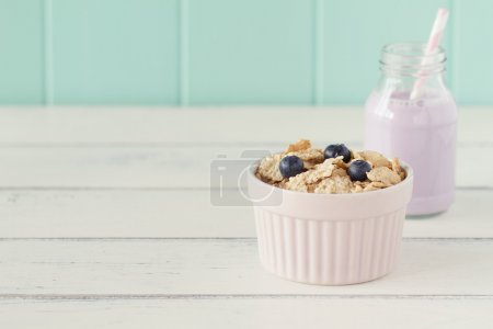 A turquoise classic whiteware baking bowl  with cereals and blueberries and a school milk bottle with blueberry smoothie and a straw on a white wooden table with a robin egg blue background. Vintage.