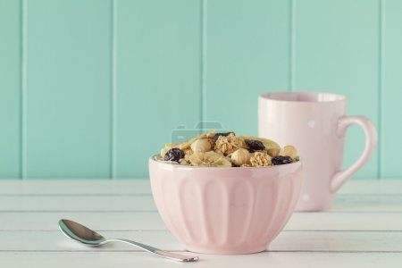 Cereals in a pink bowl on a white wooden table with a robin egg blue background. Vintage style.