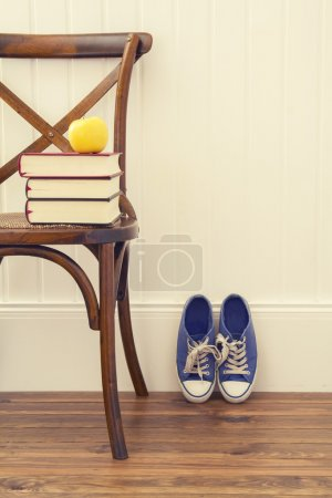 An apple on a stack of books over a chair. A pair of blue sneakers.