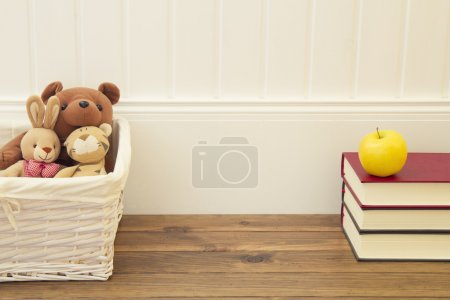 Stuffed animal toys in a basket on the floor. A stack of books and an apple in front of a white wainscot.