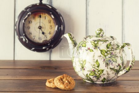 A teapot, two german cookies and a clock in the background. A wooden table with a white background. Five o'clock. Tea time. Vintage style.