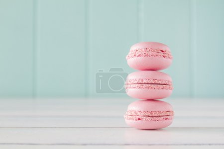A stack of macarons on a white wooden table with a robin egg blue background. Vintage Style.