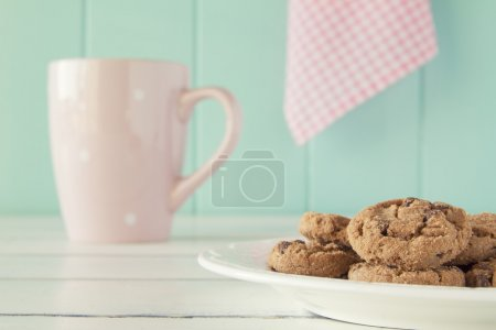 Some chocolate chip cookies on a plate and a pink mug on a white wooden table with a robin egg blue background and a pink checkered napkin. Vintage style.