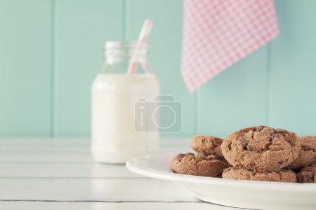 Some chocolate chip cookies on a plate and a school milk bottle with a straw on a white wooden table with a robin egg blue background and a pink checkered napkin. Vintage style.