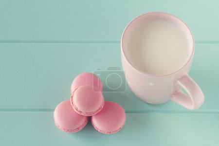 Some macarons and a pink mug with milk on a robin egg blue table. Vintage Style.