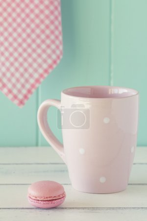 Pink mug with white polka dots, a macaron and a pink checkered napkin on a white wooden table with a robin egg blue background. Vintage Style.