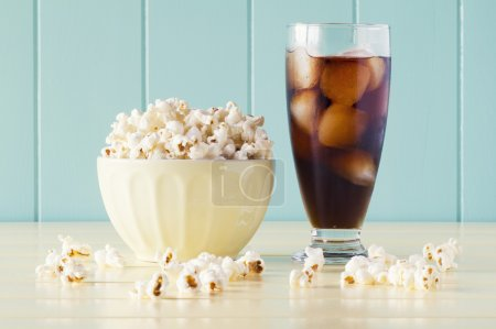 Pop corn in a bowl and a glass of cola on a yellow wooden table with a robin egg blue background. Vintage Style.