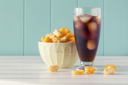 Crunchy corn snacks in a bowl and a glass of cola on a white wooden table with a robin egg blue background. Vintage Style.