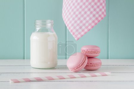 Some pink macarons and a school milk bottle on an old white wooden table with a robin egg blue background. Vintage Style.