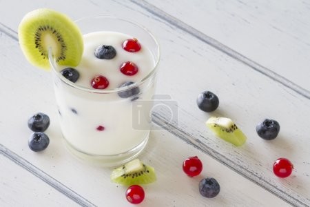A healthy breakfast: yogurt with blueberries, kiwi and red currants on a white wooden table. Vintage Style.