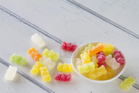 Colorful sweet gummy bears with sugar on a white wooden table. Vintage style..